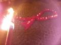 eine rote Schleife aus Stoff und Kerzen