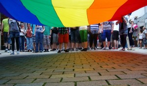 Menschen hinter einer Regenbogenfahne