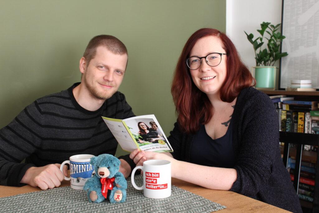 Johanna Verhoven und ihr Mann Simon sitzen am Küchentisch und betrachten den Folder zum Welt Aids Tag 2020